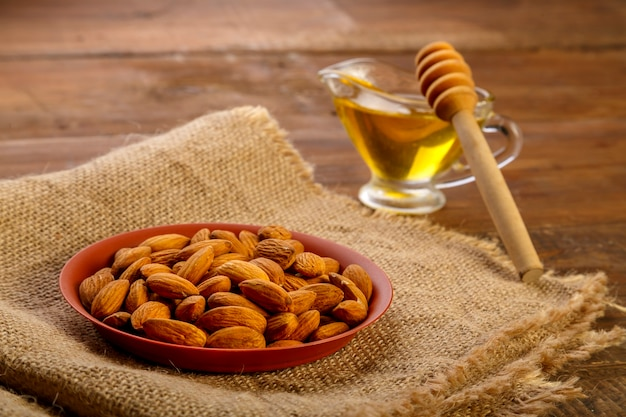 Almonds in a plate on sacking next to honey with a spoon on a wooden table.