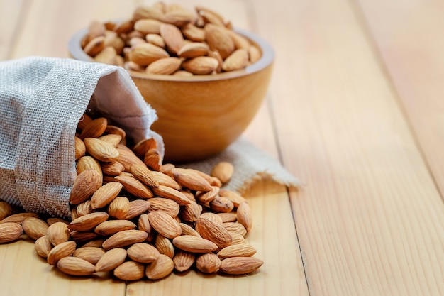 Almonds pour from bag with wood cup