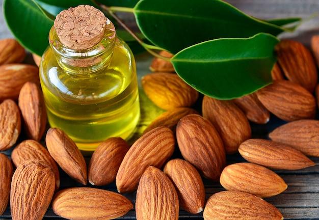 Семена миндалин и миндальное масло на старой деревянной предпосылке для здоровой еды, красоты и курорта. селективный фокус.