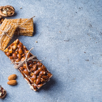 Almonds and sesame energy bar tied with string on concrete backdrop