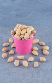 Almonds spill out of a bowl, on the marble background.