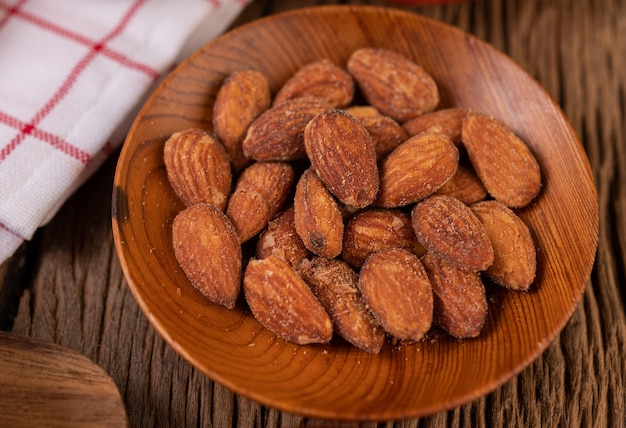 Almonds sprinkled with salt in a plate on a wooden table