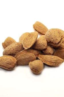 Almonds in their skins isolated on white background.