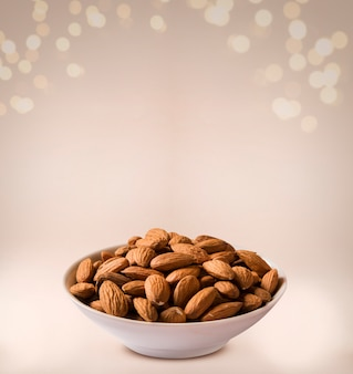 Almonds in white bowl on beige background.