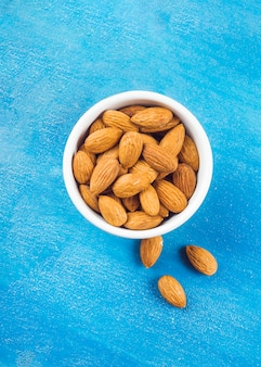 Almonds in white bowl on blue textured backdrop