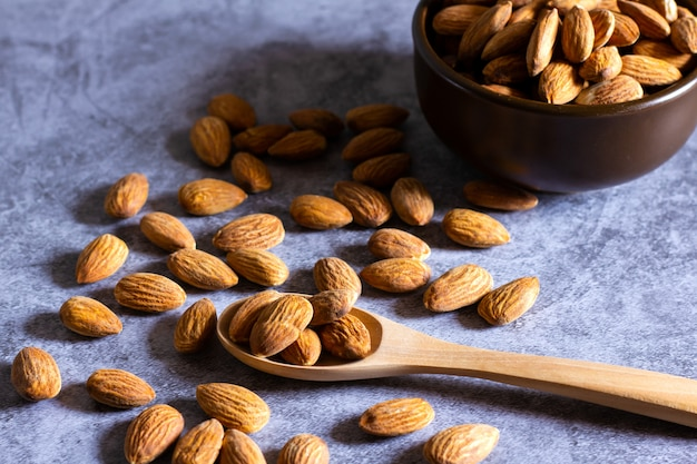 Almonds with wooden bowl and spoon on the dark table.