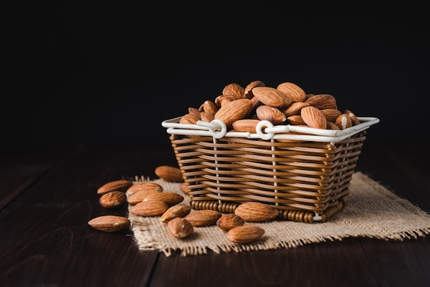 Almonds in a wooden basket on dark wooden table