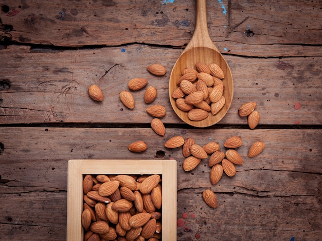 Almonds in wooden box and wooden spoon on grunge wooden background.