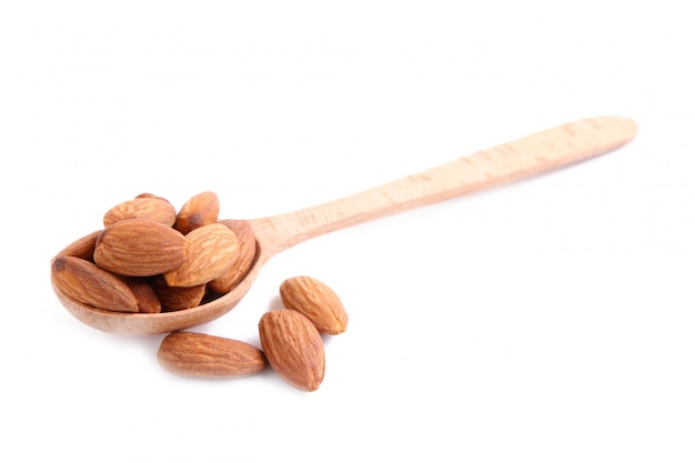 Almonds on wooden spoon isolated on white background