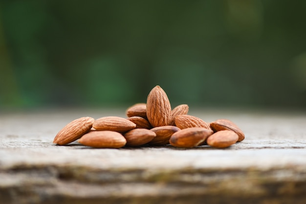Almonds on wooden table and blurred nature / close up almond nuts natural protein food and for snack