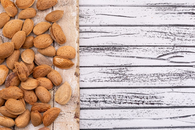 Almonds on wooden texture board on the left of white wooden