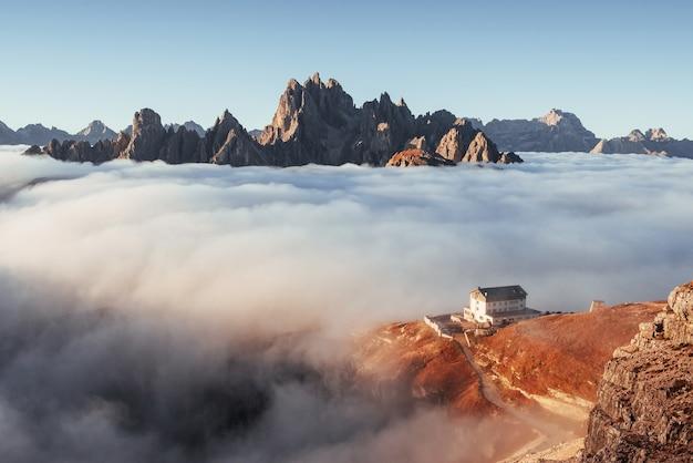 Почти все в тумане. походная тропа, идущая у холма с туманом к жилому дому.