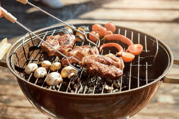 グリルバーベキューのコンセプトでおいしいバーベキュー肉のほぼ準備ができたクローズアップ写真