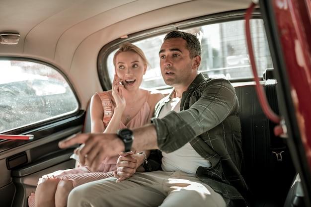 거의 다 왔어. 아내와 손을 잡고 운전사에게 차를 멈출 곳을 보여주는 진지한 승객.