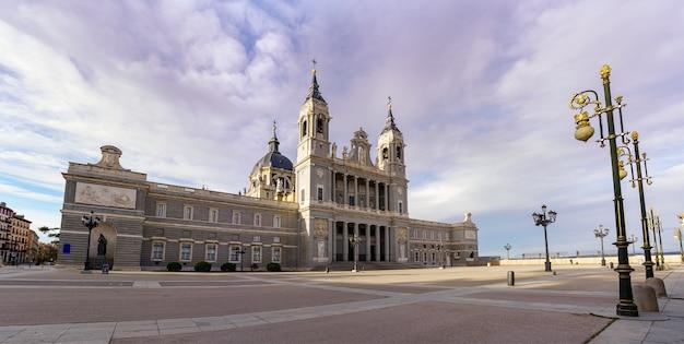 Собор альмудена в мадриде и его огромная эспланада перед фонарными столбами и голубым небом. испания.