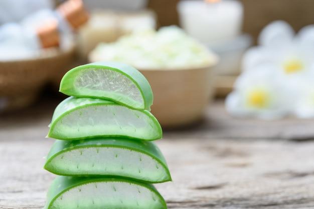 Alo vera는 소박한 나무 테이블, 선택적 초점에 꽃, 비누, 수건 및 허브 공을 얇게 썬 스파 치료 및 스킨 케어 제품