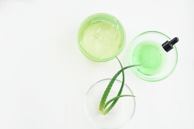 Гель алоэ, листья растений и зеленая сыворотка из натуральных экстрактов на белом фоне. увлажняющий кожу с гелем алоэ. плоская планировка, рисунок