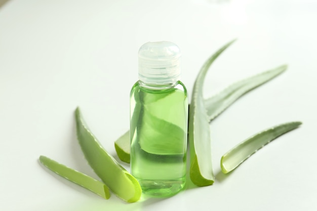 Aloe leaves and bottle with gel on white background