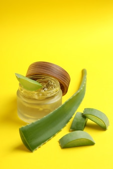 Aloe leaves and gel on yellow background