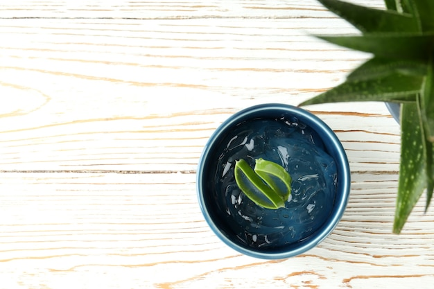 Aloe plant and bowl with gel on white wooden table