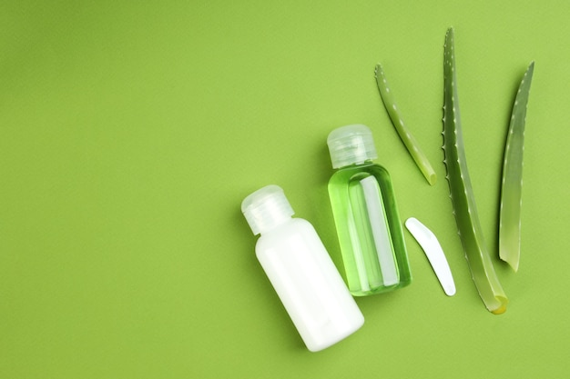 Aloe vera cosmetics and leaves on green background