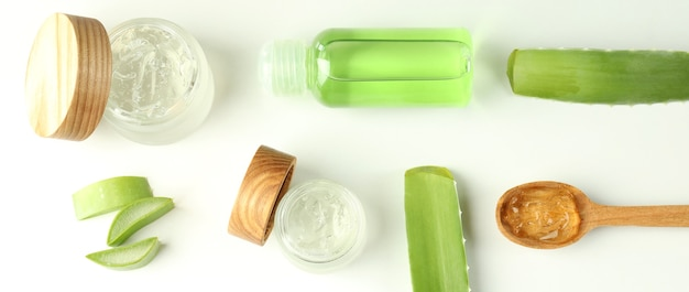 Aloe vera cosmetics, leaves and slices on white background