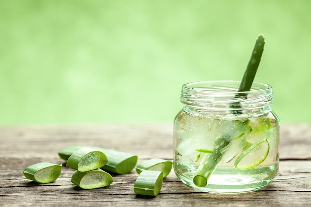 Aloe vera gel cream for skin and body care. aloe pulp slices in a glass jar and leaves on a wooden table. cosmetic lotion.