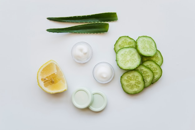 Aloe vera leaves; moisturizer cream; lemon and cucumber slices on white backdrop