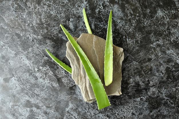 Aloe vera leaves and stone on black smokey background