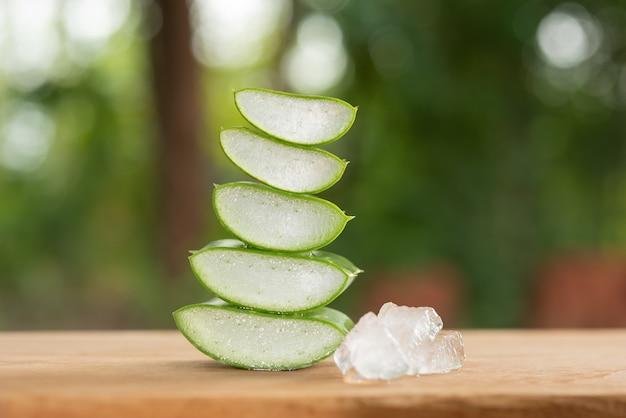 제품 디스플레이 나무 카운터 배경에 알로에 베라. 알로에 베라는 열대 녹색 식물입니다. 슬라이스 알로에 베라 천연 유기농 재생 화장품, 대체 의학. 유기농 스킨 케어 개념.