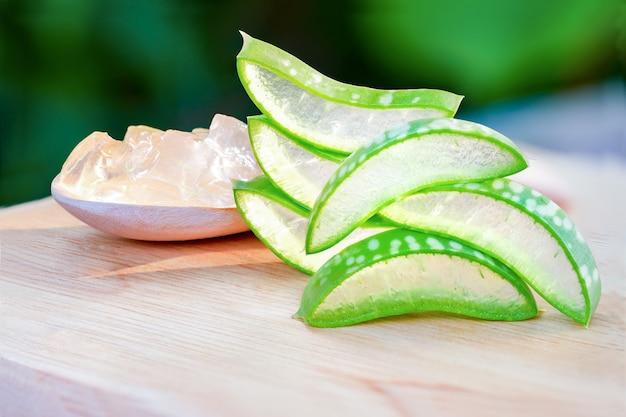 Ломтики алоэ вера (aloe barbadensis mill., star cactus, aloe, aloin, jafferabad или barbados) свежий лист с прозрачным желе в ложке, помещенной на деревянный стол, очень полезное лечебное средство на травах для ухода за кожей