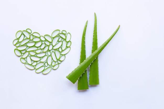 Aloe vera slices heart shape and aloe vera leaves on white background.