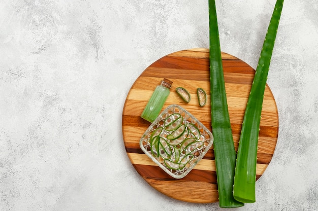 Aloe vera slices, leaves and jar with juice aloe vera on wooden board. cosmetics and herbal medicine concept. top view flat lay. copy space