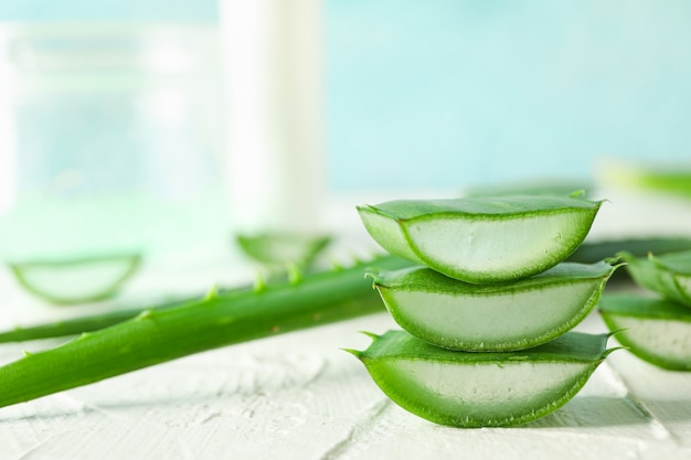 Aloe vera slices on white wooden table