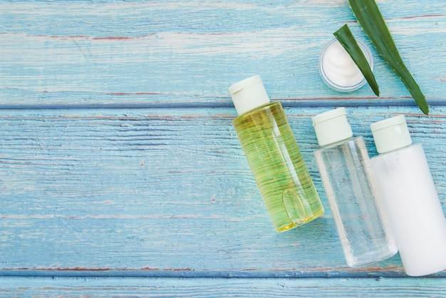 Aloe vera spray bottles and moisturizer cream on blue textured wooden backdrop