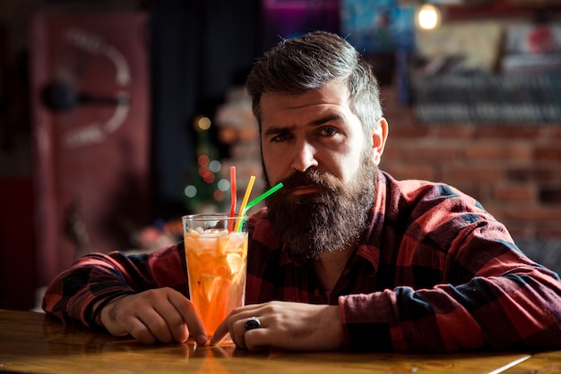 바 카운터에 앉아 혼자 수염된 남자입니다. 나이트 클럽에서 쉬고 있는 잘생긴 이발사.