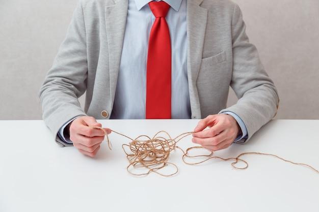 В одиночку бизнесмен пытается размотать запутанную нить клубка разгадывая ситуацию. концептуальное фото. без лица. человек сам находит выход из ситуации