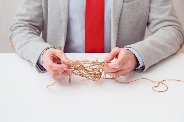 В одиночку бизнесмен пытается размотать запутанную нить клубка разгадывая ситуацию. концептуальное фото. без лица.