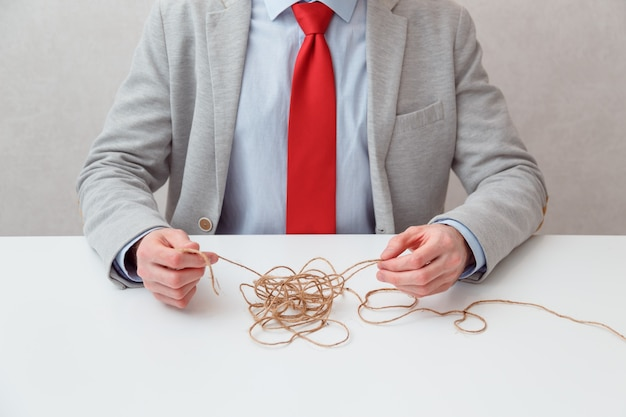 Alone businessman try to unwinds tangled thread ball like puzzle out situation. conceptual photo. no face. man finds a way out of the situation himself