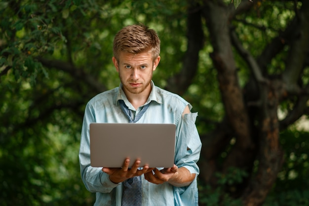 Alone businessman with laptop on desert island. business risk, collapse or bankruptcy concept