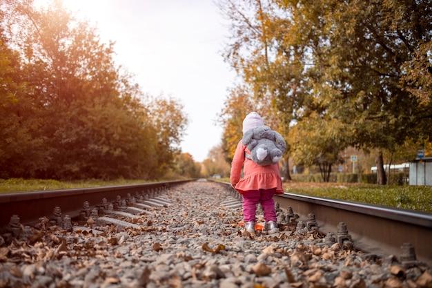 버려진 철로를 혼자 여행하는 혼자 아이 소녀