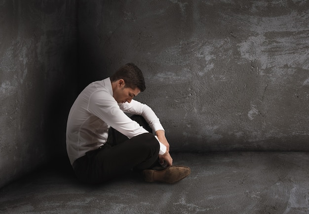 Одинокий отчаявшийся бизнесмен сидит на полу. концепция одиночества и неудач