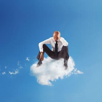 空の雲の上に座っている一人の絶望的なビジネスマン