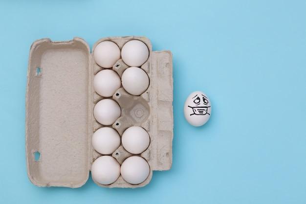 파란색 배경에 의료용 마스크와 달걀 트레이에 혼자 있는 달걀 얼굴. 코로나19 팬데믹, 자가 격리. 평면도
