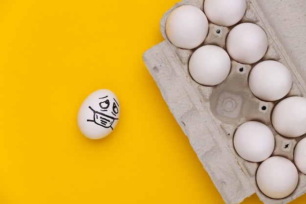 노란색 배경에 의료 마스크와 달걀 트레이에 혼자 있는 달걀 얼굴. 코로나19 팬데믹, 자가 격리. 평면도