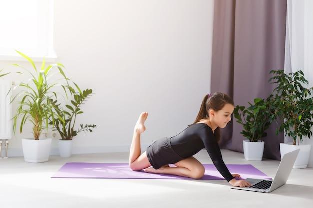 明るい部屋の床にあるラップトップでオンラインでヨガの練習をしている一人の女の子は、家の安全な世界にとどまります。