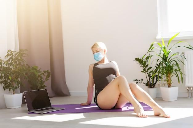 コビッド19コトナウイルスの検疫中に明るい部屋の床でヨガの練習をしている医療マスクの一人の女の子は家の安全な世界にとどまります。