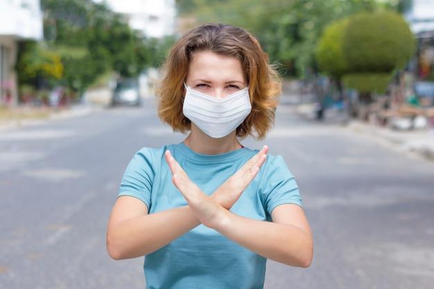 Одна девушка, молодая женщина, человек в защитной медицинской маске, стоящий на азиатской улице, показывает знак остановки x, нет, скрещенные руки. загрязнение воздуха. защита от коронавирусной пандемии китайского вируса. ncov 2019