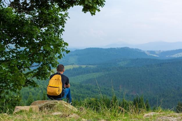 Одинокий парень сидит на скале и наслаждается мирным пейзажем зеленых гор. душевное спокойствие и расслабление.