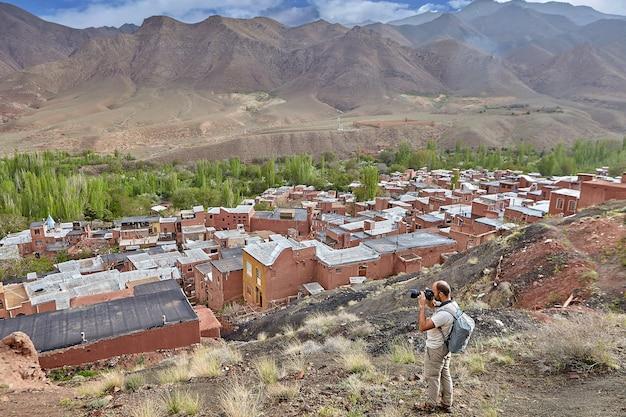 一人のハイカーが赤い粘土で作られた家で山の村の屋上を撮影します。